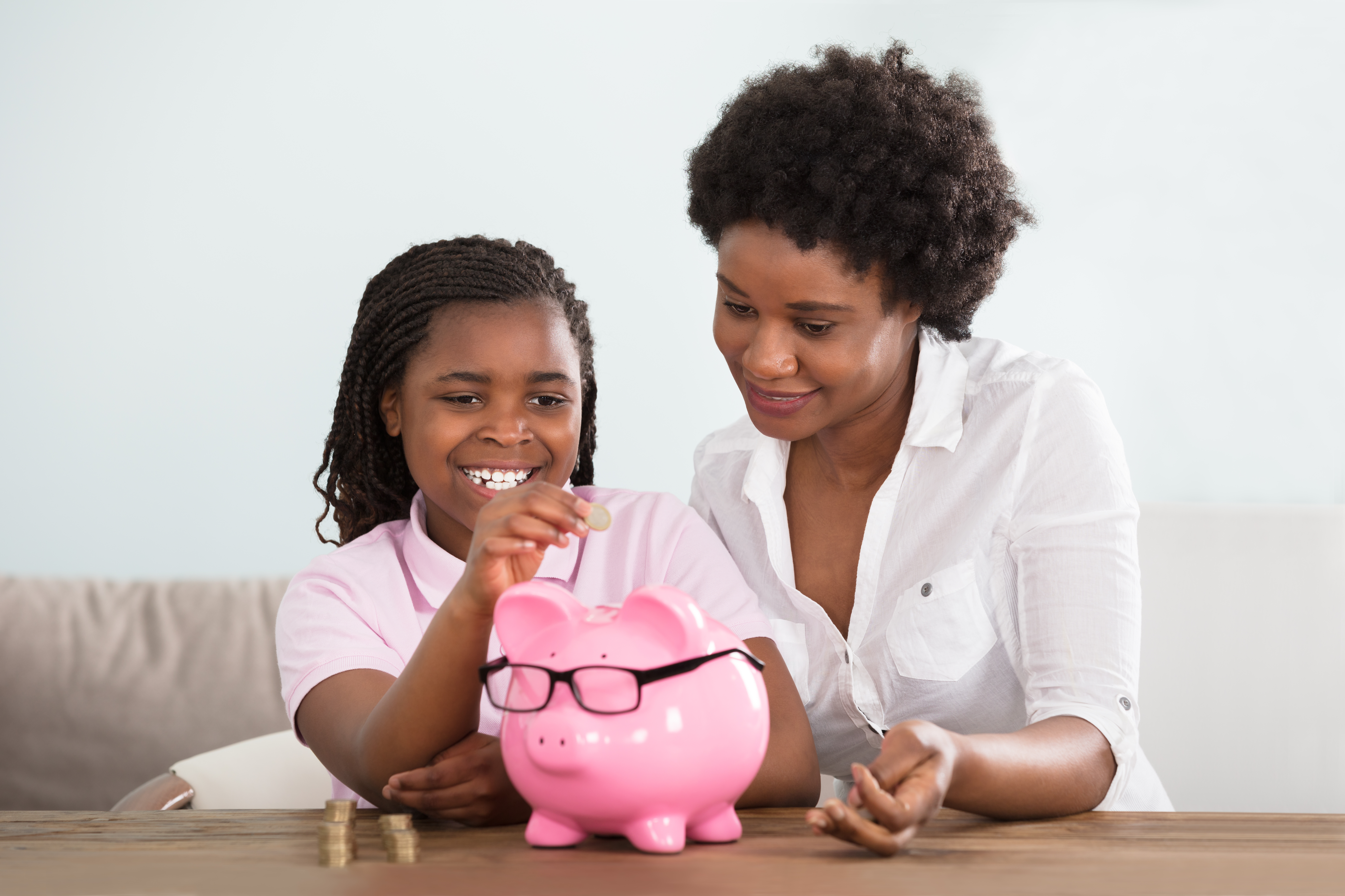 mom and kid putting money in piggy bank