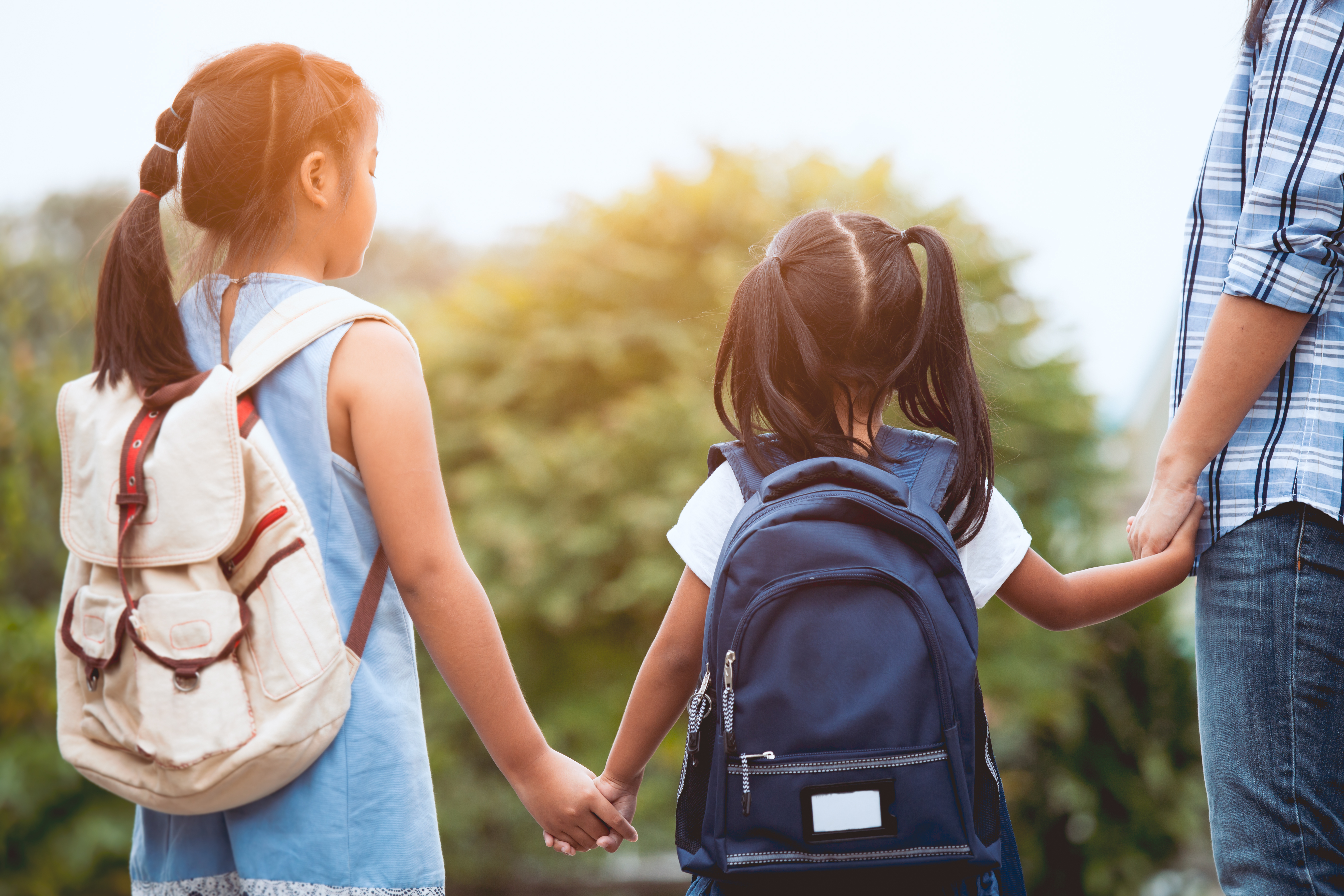 parent with children holding hands on the way to school