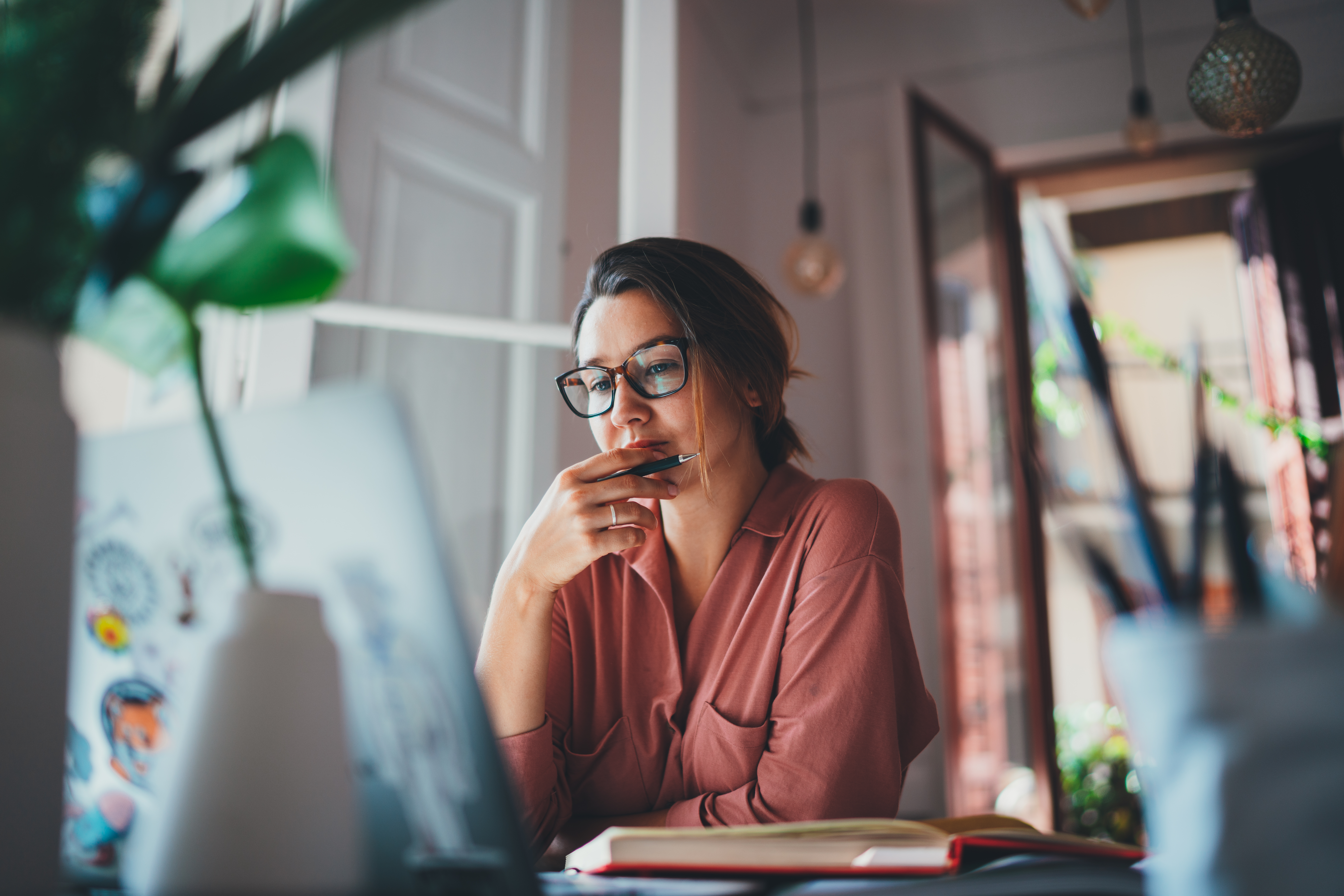 Woman with glasses looking concerned at laptop